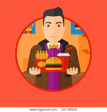A fat young man holding tray full of junk food. Smiling man in fast food restaurant. Man having lunch in a fast food restaurant. Vector flat design illustration in the circle isolated on background.