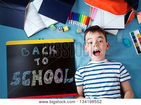 child lying on blue blanket with blackboard and various school accessories