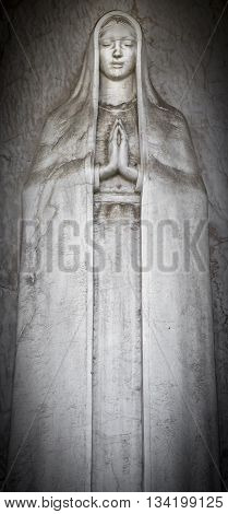 Old statue of Mary with clasped hands
