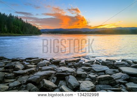 lake with rocks and trees during sunset