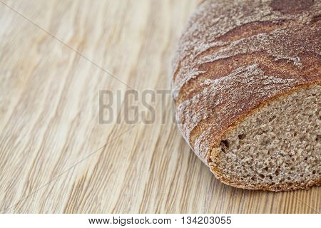 Fresh brown rye bread on a rustic wooden table