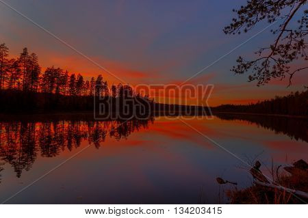 lake with rock in watertrees during sunset