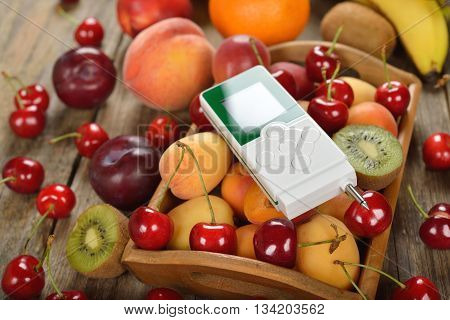 Nitrate tester and various fruits on wooden background