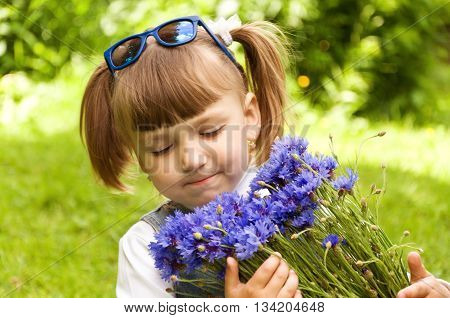 little girl holding a bouquet of blue flowers