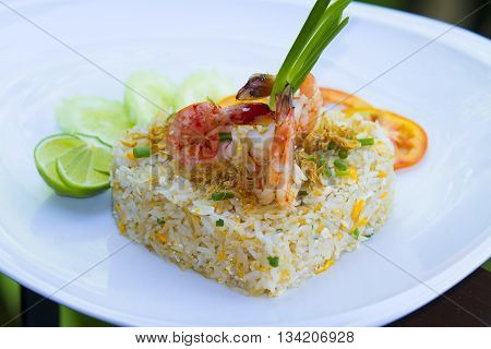 Shrimp Fried Rice on the white plate is placed in the midst of nature.