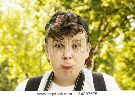 Young boy making the crazy face. Positive emotions. Funny youngster posing in nature. Pouting lips.