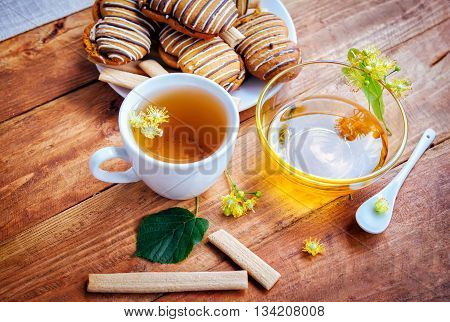 linden-blossom tea in a white cup honey in a glass bowl and pastry on a plate and on wooden background