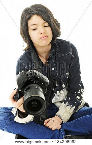 A corner image of an attractive young teen unhappy with the image in the back of her pro camera.  On a white background.