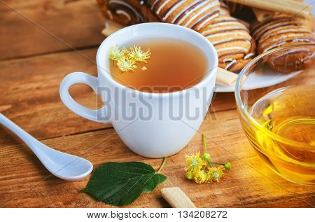 linden-blossom tea in a white cup closeup, honey in a glass bowl and pastry on a plate on wooden background
