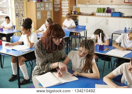 Teacher helping a girl with work at her desk, elevated view