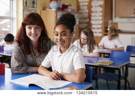 Primary school teacher and girl in class looking to camera