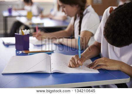 Primary school kids writing at heir desks, close up