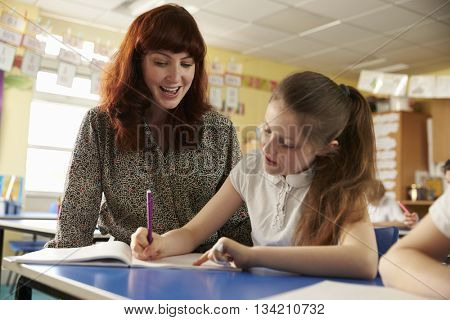 Primary school teacher helping with classwork at girlâ??s desk