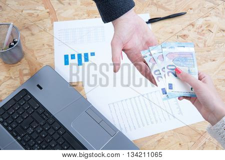 Two Hands Of Business People Holding Money Above Laptop