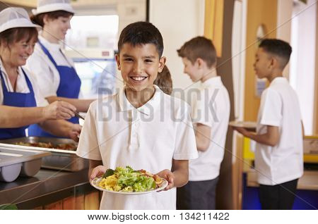 Hispanic schoolboy holds a plate of food in school cafeteria
