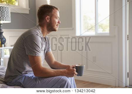Man Wearing Pajamas Sitting On Bed With Hot Drink