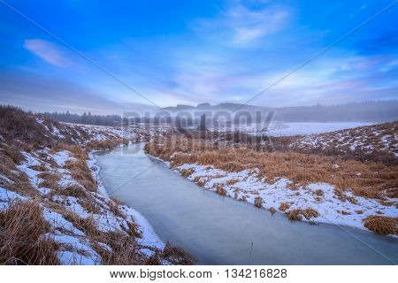 river with ice snow and hills during sunrise