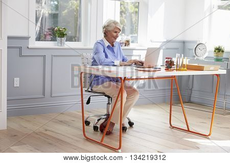 Senior Woman Sits At Desk And Works On Laptop In Home Office