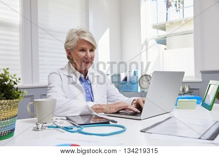 Female Doctor Sitting At Desk Working At Laptop In Office