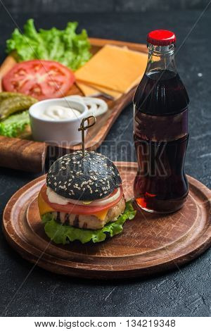 Homemade black burger with grilled chicken patty on dark background