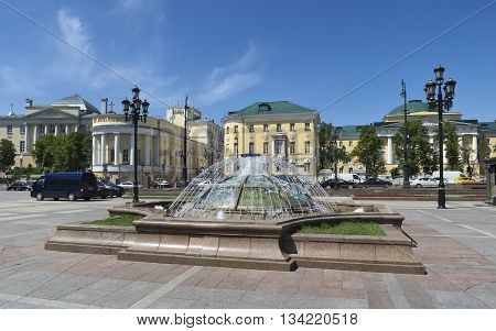 MOSCOW, RUSSIA - MAY 31, 2016: Fountain at the Manezhnaya square a view of the Moscow State University named after Lomonosov cityscape