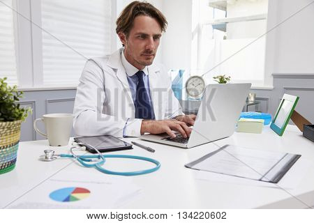 Male Doctor Sitting At Desk Working At Laptop In Office