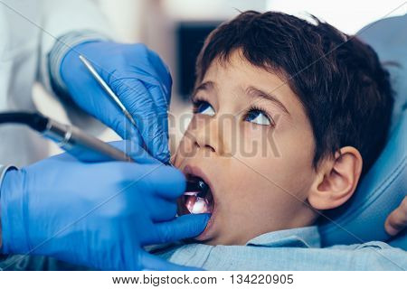 Dentist drilling little boy's tooth in dentist office