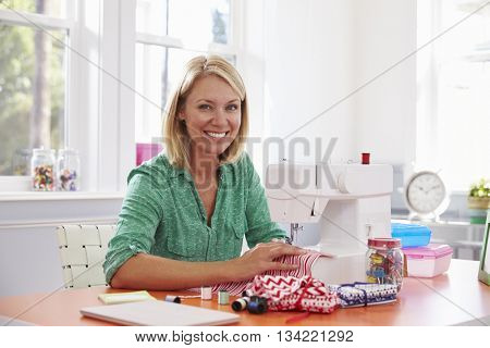 Woman Making Clothes Using Sewing Machine At Home