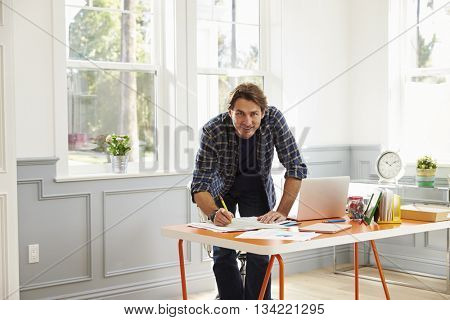 Man Standing At Desk Working At Laptop In Home Office