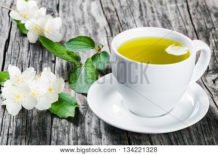 a cup of jasmine tea on a white saucer with jasmine flowers on dark wooden boards studio lights close-up