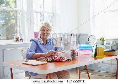 Senior Woman Making Clothes Using Sewing Machine At Home