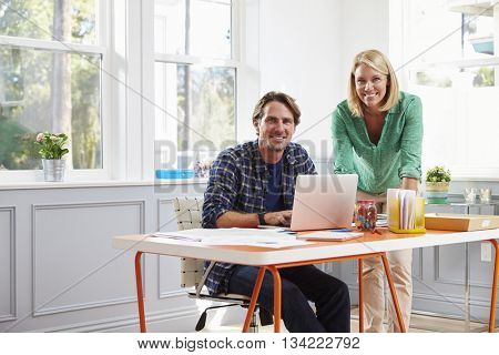 Portrait Of Couple Working Together At Desk In Home Office