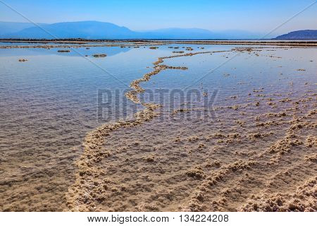 The Dead Sea at coast of Israel. The path forms freakish patterns on a water surface of the evaporated salt