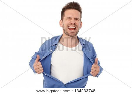 Young man shouting, tearing off shirt eyes closed.