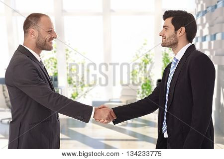 Bristly caucasian businessmen shaking hands on successful deal at bank center lobby. Smiling, standing, wearing suit and tie.