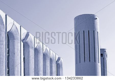 Urban architecture view of concrete walls and columns built in futuristic urban style. Architecture modern background in cold futuristic tones with architecture cityscape in modern style.