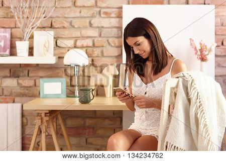 Young woman using mobilephone, sitting at home.