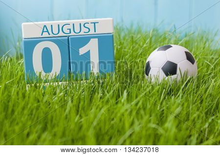 August 1st. Image of august 1 wooden color calendar on green grass lawn background with soccer ball. Summer day. Empty space for text.