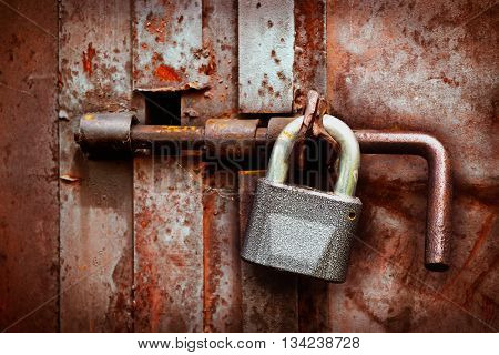 Lock and hasp on an old rusty iron gate closeup