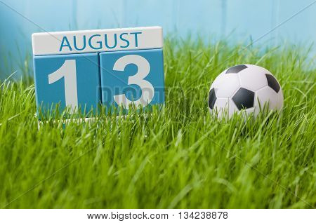 August 13th. Image of august 13 wooden color calendar on green grass lawn background with soccer ball. Summer day. Empty space for text.