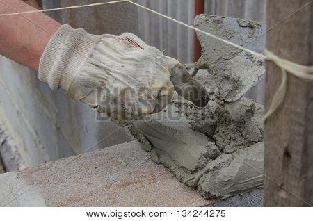 worker aligns with a spatula lay brick cinderblocks
