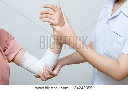Nurse applying bandage to patient injured elbow