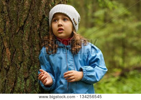 Little girl in a blue cloak, lost in the woods.