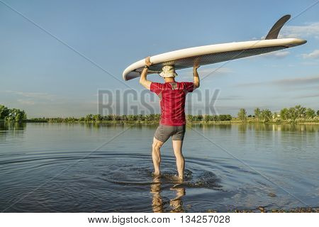 launching stand up paddleboard on a calm  lake in northern Colorado with an early summer scenery