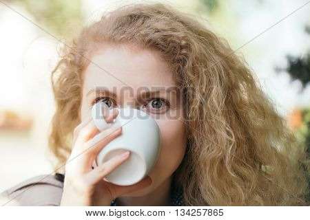Young woman with pretty face and curly long hair drinking from white coffee or tea cup outdoor