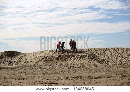 LONG BEACH, UNITED STATES - DECEMBER 26: A women volleyball team trains on the dunes on the beach in Long Beach the endurance on December 26 2015 in Long Beach.