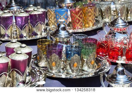 Traditional teapots with tea glasses on a tray sold in the souks of Marrakesh Morocco
