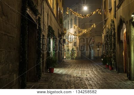 BERGAMO, ITALY - 12, JANUARY. Old European narrow empty street of medieval town with Christmas decoration on a foggy evening. Taken in Bergamo, Citta Alta, Lombardia, Italy, in January, 2016