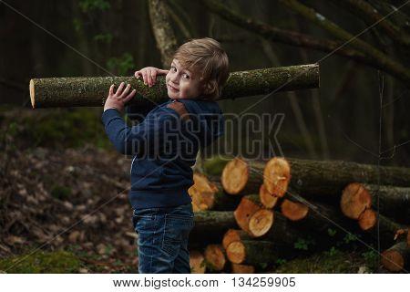 photo of little sweet lumberjack in autumn forest