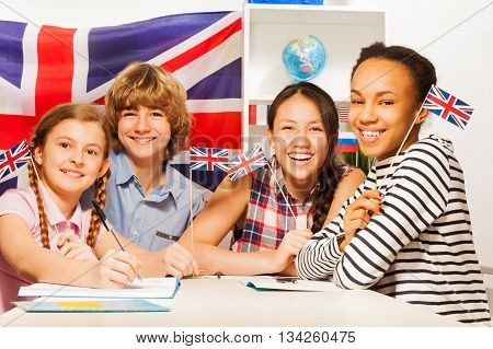 Four multiethnic teenage students sitting at the desk, holding British flags at the language courses